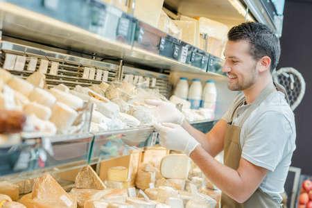 aisle: Shop assistant restocking cheese aisle