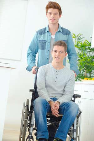 personas ayudando: Adolescente en silla de ruedas y su amigo