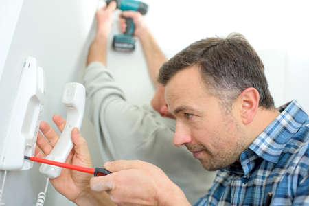 Man repairing an intercom phone Stock Photo