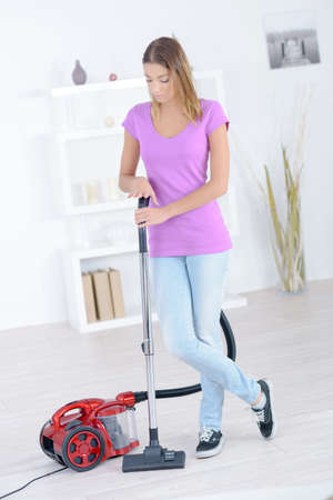 charwoman: Woman stood with a vacuum cleaner