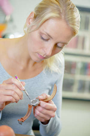 Skilled blonde woman repairing her watch