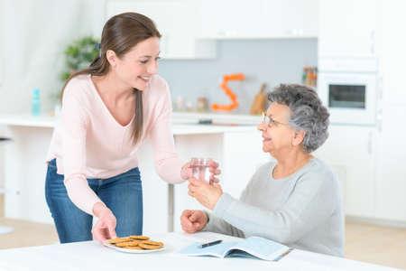 tomando agua: Se�ora mayor que tiene que tomar sus pastillas Foto de archivo