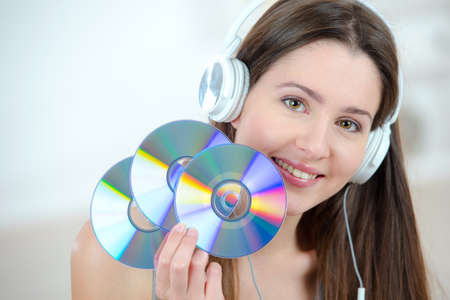 cds: Woman with headphones holding CDs