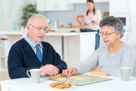seniors: Pares mayores que juegan un juego de mesa