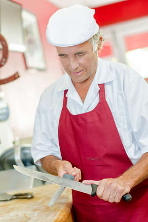 Butcher sharpening his favourite knife Stock Photo