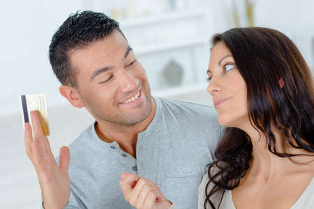 persuades: Couple with credit card debating a purchase Stock Photo
