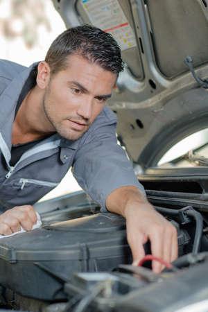 mecanico: Mecánico que trabaja en el compartimiento del motor