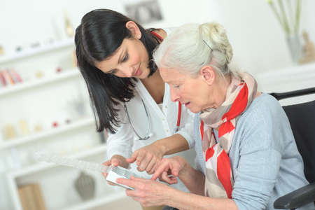 elderly adults: Doctor explaining medicine to senior woman