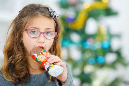 cioccolato natale: Bambina che mangia cioccolato a Natale Archivio Fotografico