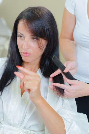 uñas largas: señora que muestra con los dedos la cantidad de cabello para recortar