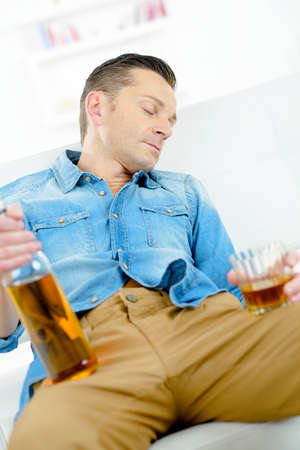 Passed out: Man asleep with bottle and glass Stock Photo