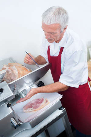 slicing: Butcher slicing ham Stock Photo