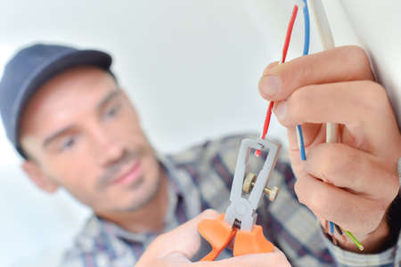 maintenance: Electrician snipping a wire