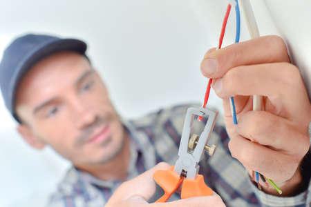 mantenimiento: Electricista cortando un alambre