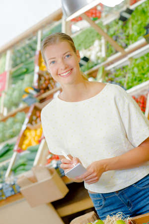 grocers: Lady in grocers with list Stock Photo