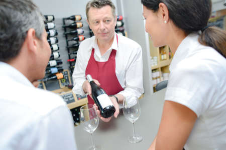 hospitality staff: Waiter presenting a bottle of red wine