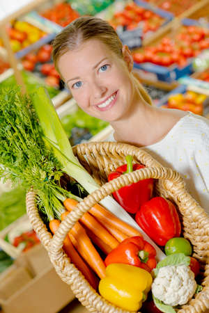 grocers: Lady showing basket full of fruit and vegetables