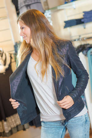 favored: Woman trying a jacket on in a shop Stock Photo