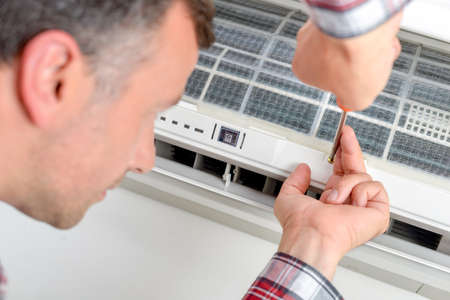 engineering tool: Installing an air conditioning unit Stock Photo