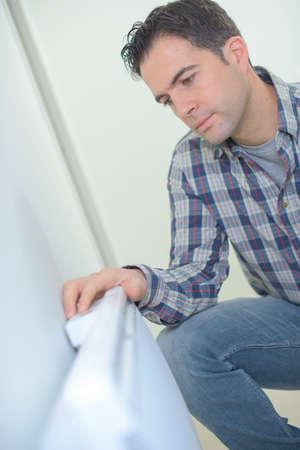 radiador: Arrodillado junto a un radiador Foto de archivo