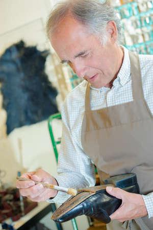 sole of shoe: Cobbler painting sole of shoe