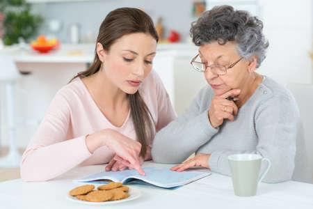 Aider sa grand-mère faire des mots croisés Banque d'images