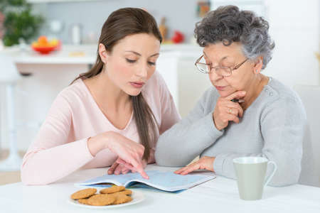 mature people: Helping her grandma do a crossword Stock Photo