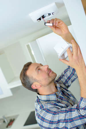 conscious: Safety conscious man fitting a fire smoke alarm