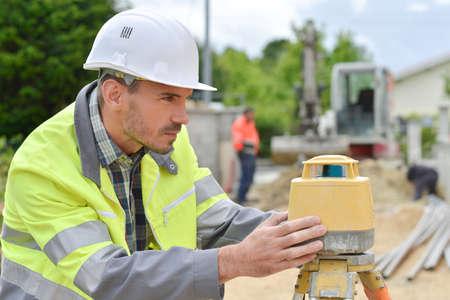 elevation meter: Surveyor lining up a machine