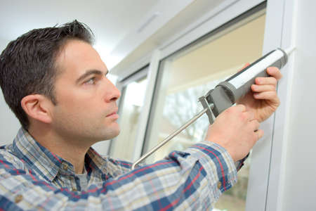 Handyman caulking a window