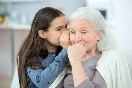 niños riendose: Niña y abuela secretos susurrantes