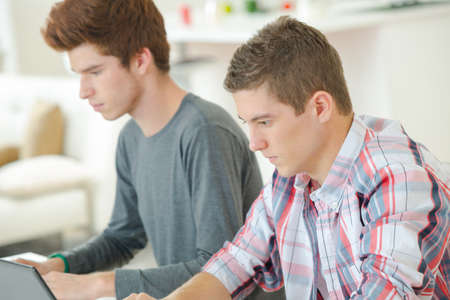 achiever: Two male students using laptops