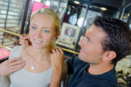 woman shop: Man offering his girlfriend some jewellery