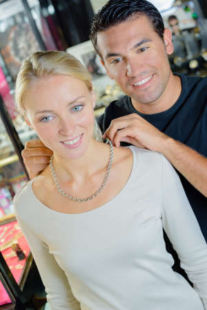 putting on: Man trying necklace on woman