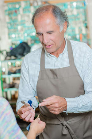 cobbler: Cobbler holding keys Stock Photo