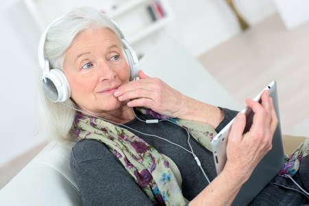 escuchando musica: Señora mayor que escucha la música a través de auriculares