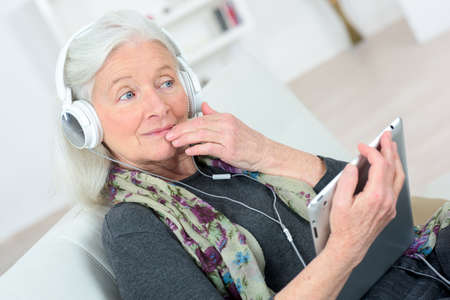happy senior: Senior lady listening to music through headphones