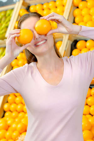 light hearted: Playful woman covering her eyes with oranges