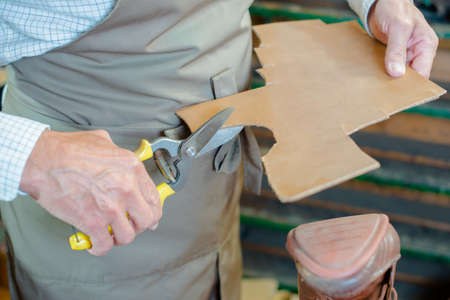 rubber lining: Cobbler cutting out new sole for shoe
