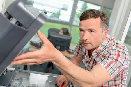 troubleshoot: Repairing a printer at work Stock Photo