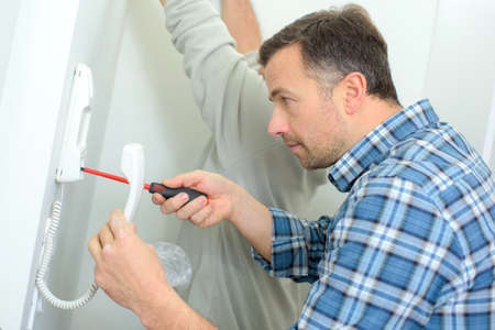entry numbers: Repairing an intercom handset Stock Photo