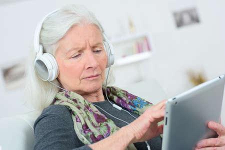 la escucha activa: Señora mayor que escucha la música a través de auriculares