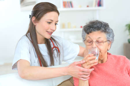 senior female: Doctor making sure senior woman takes her medication