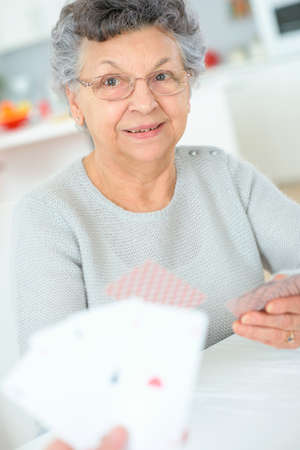 active seniors: Old lady playing a card game