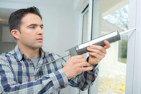 caulking: Man caulking a new window Stock Photo