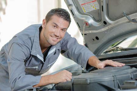 stood: Mechanic stood by a car