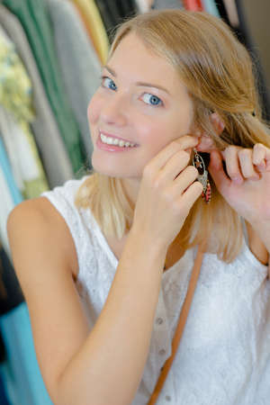 adorn: Excited woman trying on new earrings