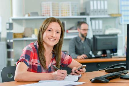 personas trabajando en oficina: Empleado de oficina leyendo un mensaje de texto