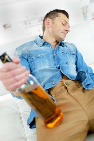 inebriated: Man asleep holding bottle Stock Photo