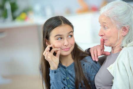小さな女の子とおばあちゃんの秘密をささやく 写真素材
